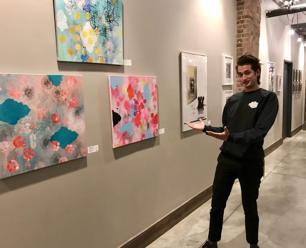 Chris Adams, who runs marketing and events for the Empire Stores building, with artwork on display at Gallery 55. This month's show is by artists affiliated with Park Slope Windsor Terrace, a Brooklyn-based artist collective. Photo by Mary Frost