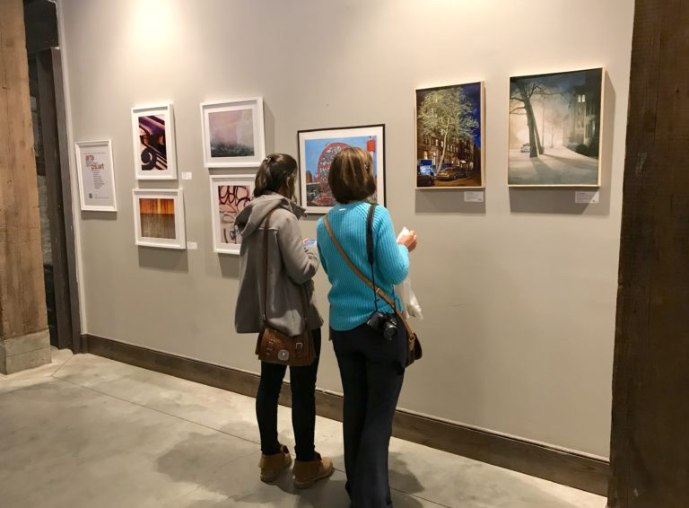 Visitors peruse artwork on the walls of Gallery 55, a curatorial project located inside Empire Stores in DUMBO. Photo by Mary Frost